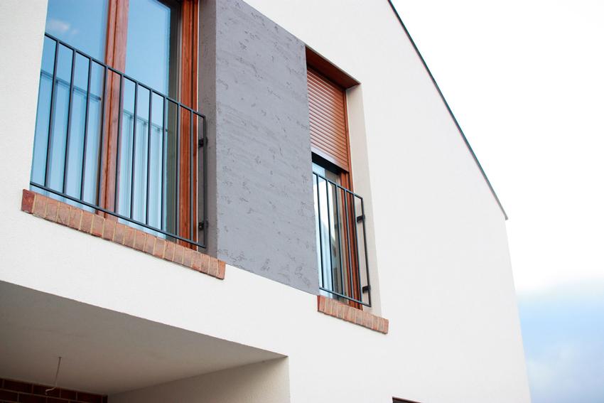 Nowoczesny dom jednopiętrowy - zbliżenie na balkony na piętrze